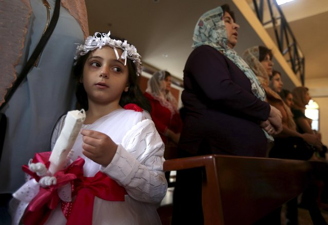 An Assyrian Christian girl holds a candle as she attends Mass marking the traditional Palm Sunday procession at the Assyrian church in east of Beirut, Lebanon, Sunday, March 29, 2015. Streams of Christians gathered Sunday to celebrate the path of Jesus Christ's last journey into Jerusalem, when his followers laid palm branches in his path, before his crucifixion. (Photo by Hussein Malla/AP Photo)