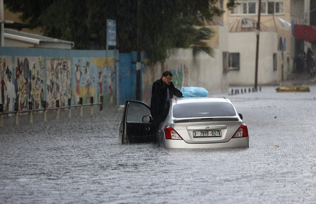 A Palestinian driver stands on his stranded car flooded with water due to heavy raining in Gaza City, Thursday, December 5, 2013. Heavy rains flooded most streets and blocked some of the streets of the refugee camps and the cities of Gaza Strip. (Photo by Adel Hana/AP Photo)