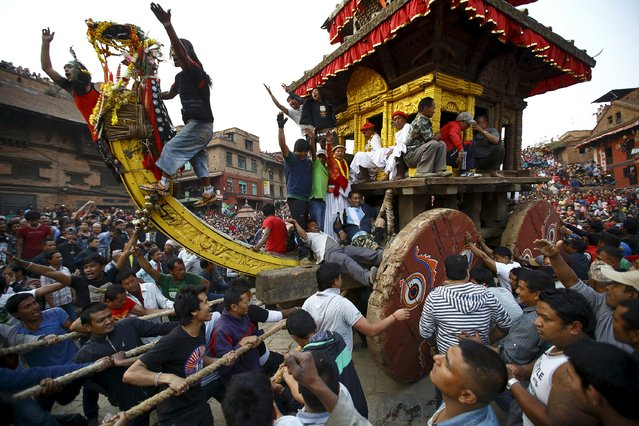 The chariot of God Bhairab is pulled through the city centre of Bhaktapur near Kathmandu during the Bisket festival April 10, 2015. The festival, which runs for more than a week and coincides with the Nepalese New Year, involves devotees offering prayers and the pulling of two chariots, one carrying the idol of God Bhairab and the other with the idol of Goddess Bhadrakali, around the ancient city of Bhaktapur. (Photo by Navesh Chitrakar/Reuters)
