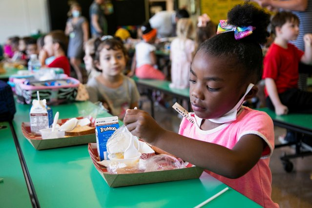 A student takes away her mask as she eats lunch at Wilder Elementary School in Louisville, KY, Kentucky, U.S., August 11, 2021. (Photo by Amira Karaoud/Reuters)