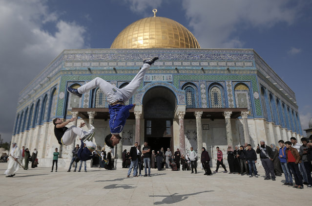 Palestinian youths pratice parkour outside the Dome of the Rock mosque at the Al-Aqsa mosque compound following Friday prayers in the Old City of Jerusalem on November 21, 2014. Tens of thousands of Muslims prayed at Jerusalem's flashpoint Al-Aqsa mosque Friday, after Israeli eased age restrictions on entry for a second straight week despite high tension after a wave of violence. (Photo by Ahmad Gharabli/AFP Photo)