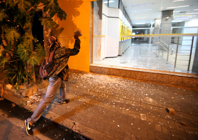 A demonstrator throws stone at a Brasil bank entrance during a protest against the increase in the transport fare in Sao Paulo, Brazil, January 12, 2017. (Photo by Paulo Whitaker/Reuters)