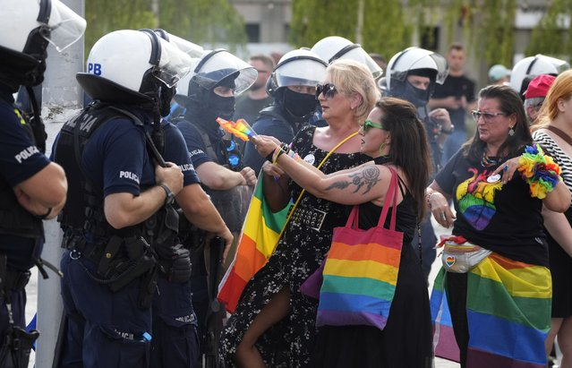 Participants in colorful 3rd Equality Parade march with rainbow flags under heavy police presence in support of LGBT rights at the foot of Poland's most revered Catholic shrine, the Jasna Gora Monastery in Czestochowa, Poland, Saturday, August 21, 2021. (Photo by Czarek Sokolowski/AP Photo)