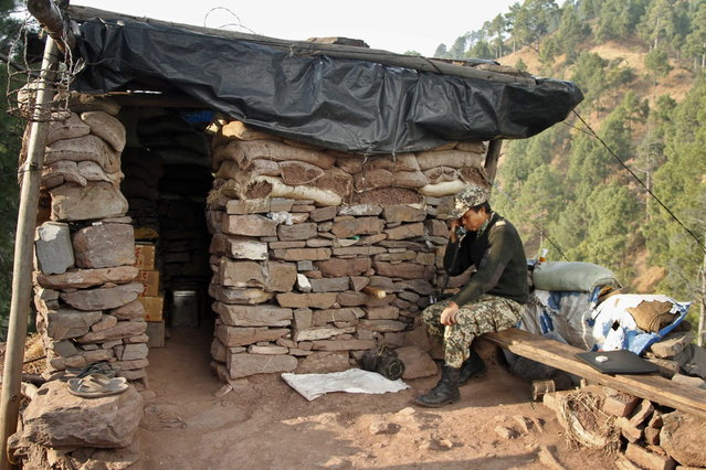 In this December 22, 2013 photo, an Indian Border Security Force (BSF) soldier speaks to family members at one of the forward posts near the Line of Control (LOC), that divides Kashmir between India and Pakistan, at Krishna Ghati (KG Sector) in Poonch, 290 kilometers (180 miles) from Jammu, India. (Photo by Channi Anand/AP Photo)
