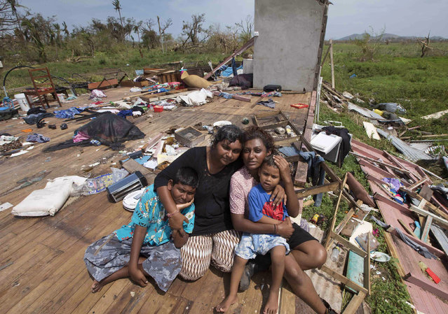 Sanjogeeta Kiran, right, with her sister Sulva Kiran, second left, and her children Shivendera, left, and Raajeen, sit amid the debris of their home in RakiRaki, Fiji, Wednesday, February 24, 2016, after cyclone Winston ripped through the island nation. (Photo by Brett Phibbs/New Zealand Herald via AP Photo)