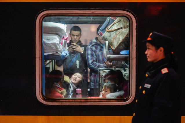 Passengers wait for a train to depart from the Hankou Railway Station in Wuhan, central China's Hubei province, Friday January 13, 2017. Officials expect that Chinese travelers will make almost 3 billion trips during the holiday travel rush that starts runs through Feb. 21. These trips include intercity flights, trains and local bus rides to villages for China's 1.4 billion people. (Photo by Chinatopix via AP Photo)