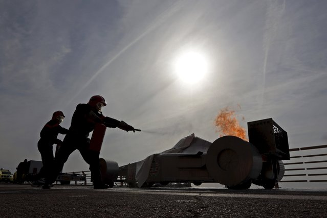 Track marshals use fire extinguishers during a drill in preparation for the upcoming Monaco Formula One Grand Prix in Monaco April 11, 2015. The Monaco F1 Grand Prix will take place in the Monaco principality on May 24. (Photo by Eric Gaillard/Reuters)