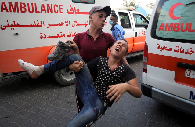 A protestor helps a wounded youth, who was shot by Israeli troops in his foot during a protest at the Gaza Strip's border with Israel, into the treatment room of Shifa hospital in Gaza City, Saturday, August 21, 2021. (Photo by Abdel Kareem Hana/AP Photo)