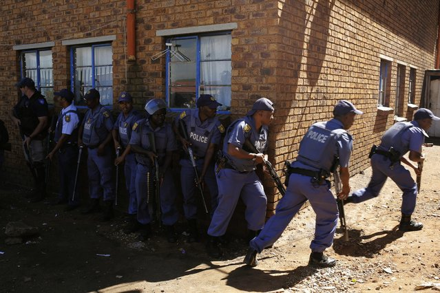 Police officers advance to enter mens hostels after xenophobic violence in the area overnight forced foreign shop owners to close their shops for fear of attack in Actonville, Johannesburg, South Africa, 16 April 2015. (Photo by Kim Ludbrook/EPA)