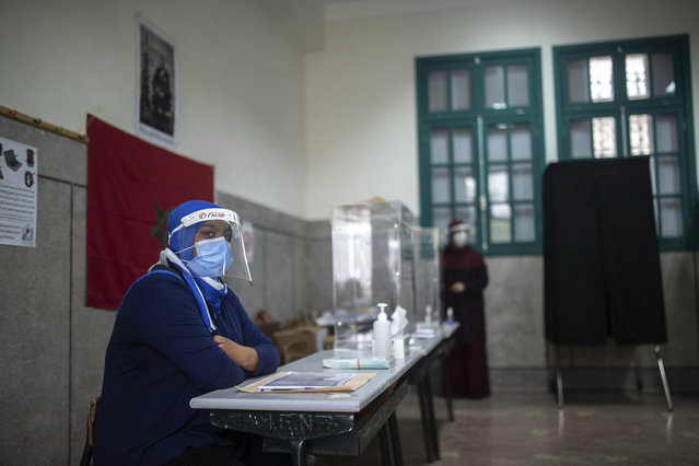Election officials wearing face masks wait for voters inside a polling station, in Rabat, Morocco, Wednesday, September 8, 2021. Moroccans are choosing a new parliament and new local leaders in elections reshaped by the pandemic. Candidates are promising to create jobs and boost Morocco's economy, education and health care. The governing Islamist party is eyeing a third term at the helm of the government if it again wins the most parliament seats. (Photo by Mosa'ab Elshamy/AP Photo)