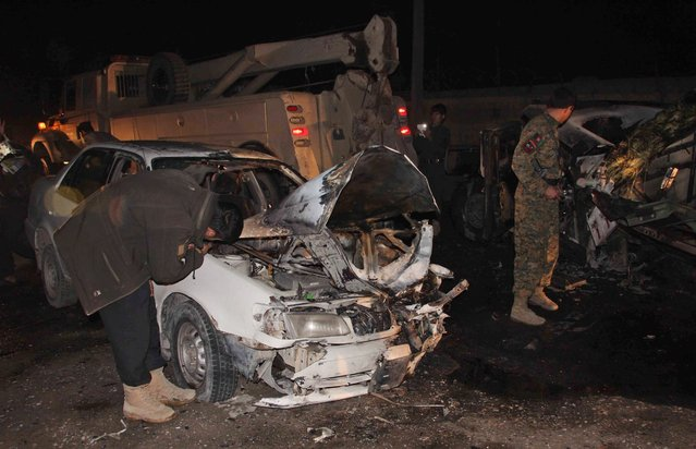 A picture made available on 29 February 2016 shows Afghan security officials inspecting the site of a bomb blast that apparently targeted a police vehicle, in Lashkargah, Helmand province, Afghanistan, on 28 February 2016. According to local sources at least three policemen were killed and ten civilians were injured in the incident. (Photo by Watan Yar/EPA)