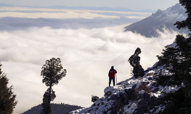 Fog blankets Seydisehir town as a hiker is seen on the top of Kupe mountain in Konya, Turkey on December 24, 2018. (Photo by Fahri Kubilay/Anadolu Agency/Getty Images)