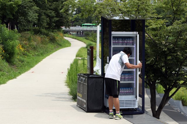 A resident takes a bottle of water from a refrigerator set up for villagers at a neighborhood park in Seoul, South Korea, 20 July 2021, amid a heat wave. Such fridges, which are installed here and there, will provide free water until the end of August. (Photo by Yonhap/EPA/EFE)