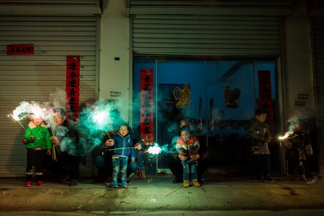 Children play with fire crackers on the eve of the Chinese Lunar New Year, or the Spring Festival, in Lianyungang, Jiangsu province, China, January 27, 2017. (Photo by Reuters/Stringer)