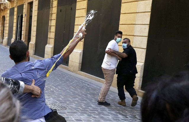 A bank customer throws eggs towards the guards of a bank, during a protest in Beirut, Lebanon, Wednesday, October 6, 2021. (Photo by Bilal Hussein/AP Photo)
