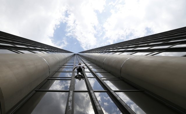 """French climber Alain Robert, also known as """"Spiderman"""", scales the Tour Montparnasse, a 210-metre (689 ft) building in central Paris, France April 28, 2015. Robert scaled the tower with a flag of Nepal in tribute to the victims of the earthquake. (Photo by Gonzalo Fuentes/Reuters)"""