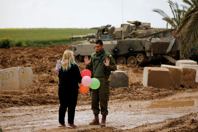 A woman gives balloons to an Israeli soldier near the border between Israel and Gaza on its Israeli side, March 15, 2019. (Photo by Amir Cohen/Reuters)