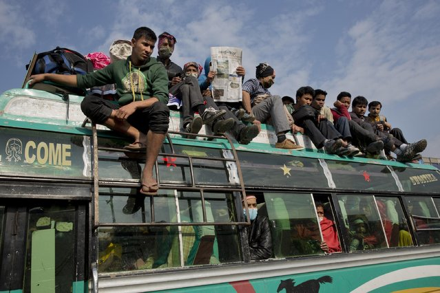 Nepalese load into buses going to their hometowns in Kathmandu, Nepal, Wednesday, April 29, 2015. Thousands of people are lining up at bus stations in Kathmandu where the government is providing free transportation for people hoping to travel to their hometowns and villages. (Photo by Bernat Amangue/AP Photo)