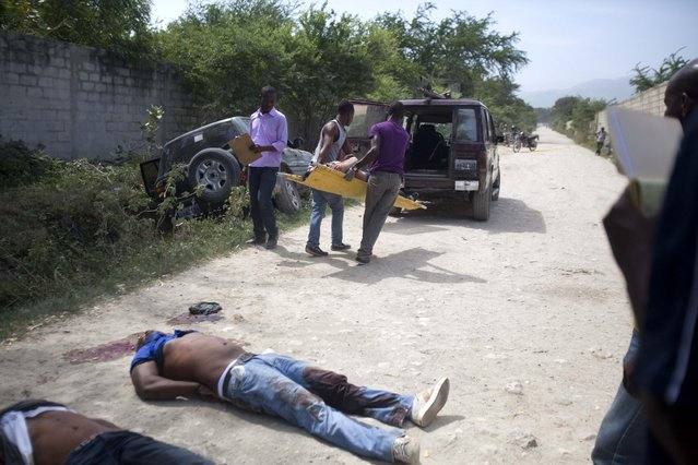 Morgue workers carry a woman's body to their vehicle at a crime scene where two other men were also found dead in Tabarre, a town on the outskirts of Port-au-Prince, Haiti, early Friday, May 1, 2015. Investigators removed three bodies, found handcuffed and blindfolded, from a car, far left, parked on the side of a street surrounded by open land and about three blocks from the U.S. embassy. (Photo by Dieu Nalio Chery/AP Photo)