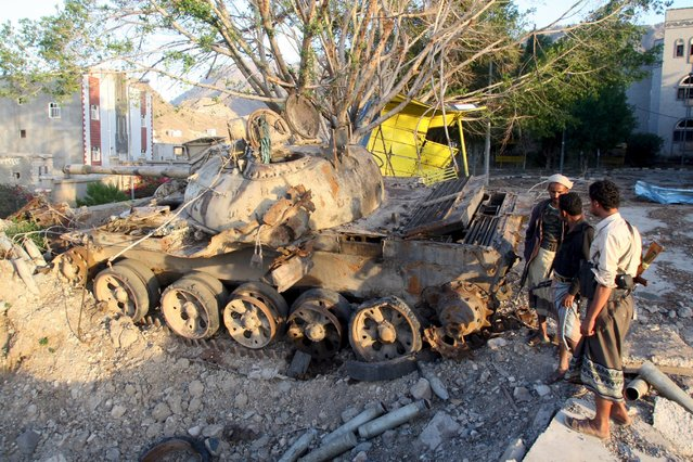 Pro-government fighters stand next to a tank destroyed during recent fighting in Yemen's southwestern city of Taiz March 14, 2016. (Photo by Anees Mahyoub/Reuters)