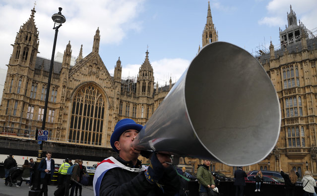 A pro EU protestor shouts through a megaphone at the Houses of Parliament in London, Wednesday, March 27, 2019. British lawmakers were preparing to vote Wednesday on alternatives for leaving the European Union as they seek to end an impasse following the overwhelming defeat of the deal negotiated by Prime Minister Theresa May. (Photo by Frank Augstein/AP Photo)