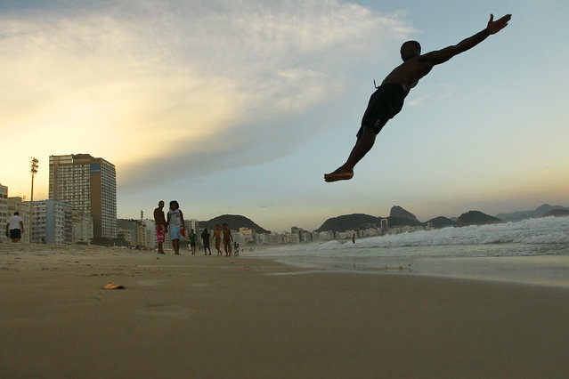 Circus performer Maicon Gomes does a set of flips for his friends on Copacabana Beach following the Alegria da Zona Sul pre-Carnival street parade on February 2, 2014 in Rio de Janeiro, Brazil. Carnival officially begins on February 28 but pre-festivities have already begun. (Photo by Mario Tama/Getty Images)