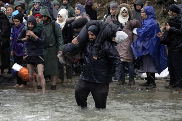 Refugees and migrants attempt to cross a river near the Greek-Macedonian border to enter Macedonia after an unsuccessful attempt yesterday, west of the village of Idomeni, Greece, March 15, 2016. (Photo by Alexandros Avramidis/Reuters)