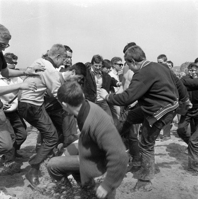 A youth lying on the sand at Margate, Kent, May 18, 1964, is the centre of a fight which broke out when Mods and Rockers clashed on the beach at the seaside resort. Police arrested many of the youths. (Photo by AP Photo)