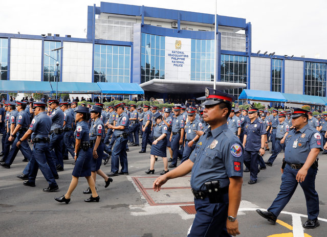 Policemen walk past Philippine National Police headquarters after taking part in the founding anniversary of the Philippine National Police celebration at Camp Crame, in Quezon city Metro Manila, Philippines February 6, 2017. (Photo by Erik De Castro/Reuters)