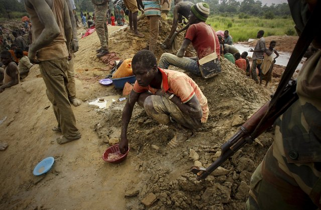 A gold prospector sits and eats close to a soldier at a gold mine near the village of Gamina, in western Ivory Coast, March 18, 2015. (Photo by Luc Gnago/Reuters)