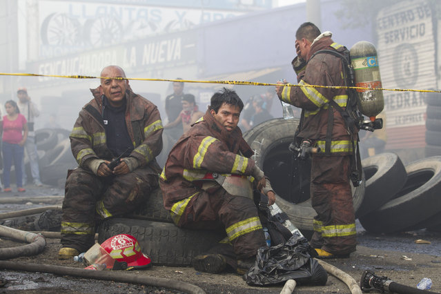 Firemen rest after working to control a fire at a tire warehouse in La Terminal, the largest and most important market in Guatemala City, Wednesday, May 6, 2015. (Photo by Moises Castillo/AP Photo)