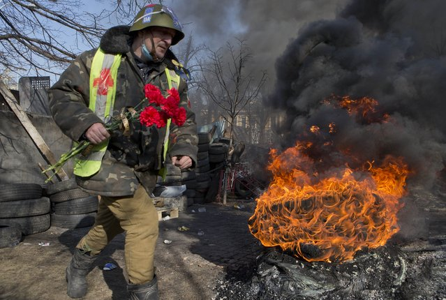 An anti-government protester moves past burning car tires as he carries flowers to be laid at the spot where some of his comrades were killed the previous day, at a barricade in central Kiev, Ukraine, Friday, February 21, 2014. European officials say Ukrainian protesters have agreed to a deal with Ukraine's president on defusing a deadly political crisis. Earlier Friday President Viktor Yanukovych announced early elections and promised to invite the opposition into the government. (Photo by Darko Bandic/AP Photo)