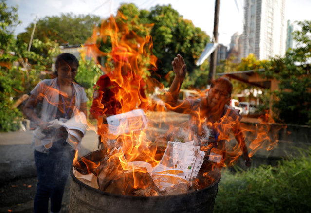 Electoral staff burn unused ballots after polling stations closed during the general election in Boca La Caja neighborhood, Panama City, Panama on May 5, 2019. (Photo by Jose Cabezas/Reuters)