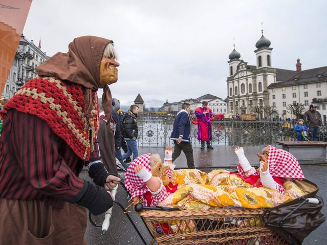 A participant pushes a pram with dolls as he walks on the streets of Lucerne. (Photo by Sigi Tischler/Keystone)