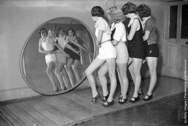 1935:  Students at a dance school dancing in front of a large, round mirror