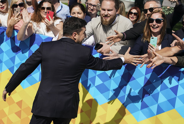 Ukrainian President-elect Volodymyr Zelenskiy greets supporters before his inauguration ceremony in Kiev, Ukraine, Monday, May 20, 2019. Television star Volodymyr Zelenskiy has been sworn in as Ukraine's next president after he beat the incumbent at the polls last month. The ceremony was held at Ukrainian parliament in Kiev on Monday morning. (Photo by Evgeniy Maloletka/AP Photo)