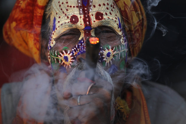 A Hindu holy man smokes marijuana at the courtyard of the Pashupatinath temple during Shivaratri festival in Kathmandu, Nepal, Friday, February 24, 2017. Shivaratri, or the night of Shiva, is dedicated to the worship of Lord Shiva, the Hindu god of death and destruction. (Photo by Niranjan Shrestha/AP Photo)
