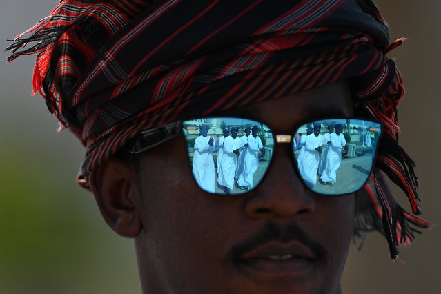 Dancers are reflected in a pair of sunglasses as crowds gather to watch the 10th Tour of Oman cycle race in Muscat, Oman on February 19, 2019. (Photo by Justin Setterfield/Getty Images)
