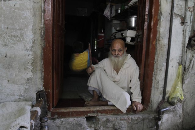 A man sits in a doorway during a power outage in Lahore, Pakistan Wednesday, May 20, 2015. Most parts of Pakistan have been hit by an electricity crisis, causing power outages that last between 6 to 12 hours per day. (Photo by K. M. Chaudary/AP Photo)