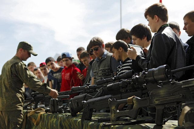 High school students, who are potential conscripts, look at firearms during an open army day at a military base in Stavropol, Russia, April 15, 2016. (Photo by Eduard Korniyenko/Reuters)