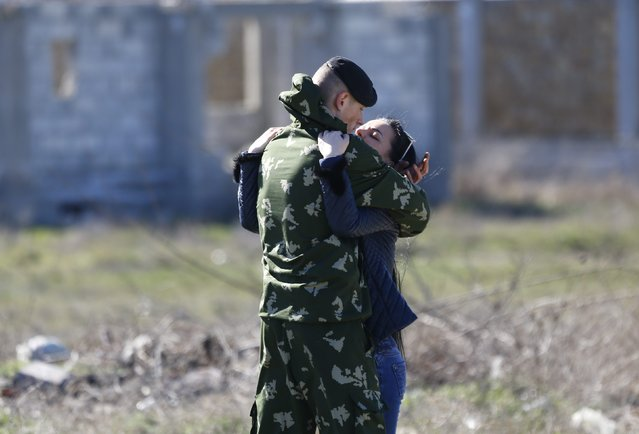 A woman hugs a Ukrainian marine in front of a Ukrainian marine base in the Crimean port city of Feodosia, March 23, 2014. Russia's defence ministry said on Sunday that it was complying with international troop limits near its border with Ukraine, after NATO's top military commander voiced concern over what he said was a large Russian force on Ukraine's eastern border. (Photo by Shamil Zhumatov/Reuters)