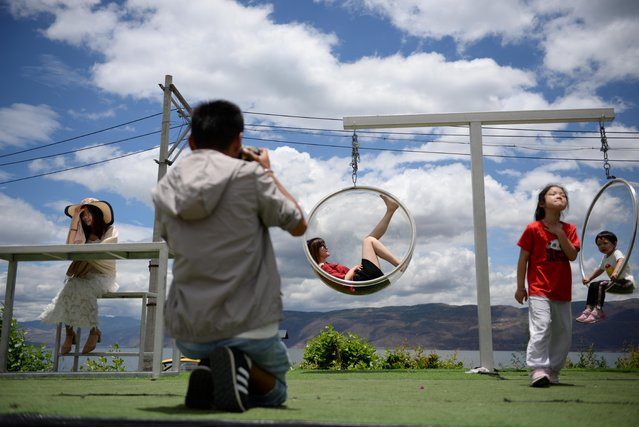 Tourists pose with props for pictures at a photo booth near Erhai Lake in Dali Bai Autonomous Prefecture, Yunnan province, China on June 15, 2019. Chinese tourists are flocking to a lake in southwest Yunnan province to recreate photos that have gone viral on social media, the country's latest selfie craze. Visitors to Erhai lake say photography sets offering everything from rare animals to fields of brightly-coloured flowers are essential to creating their Kodak moment. (Photo by Tingshu Wang/Reuters)
