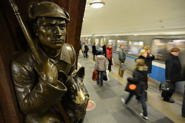 Subway passengers walk past bronze sculptures representing the Soviet people at the Ploshchad Revolyutsii metro station in Moscow, on November 14, 2012. (Photo by Kirill Kudryavtsev/AFP Photo)