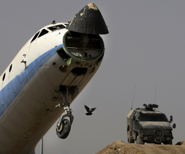 German ISAF soldiers secure an airfield next to a destroyed passenger plane left by the Russians in Kunduz on September 19, 2008. (Photo by Anja Niedringhaus/AP Photo)