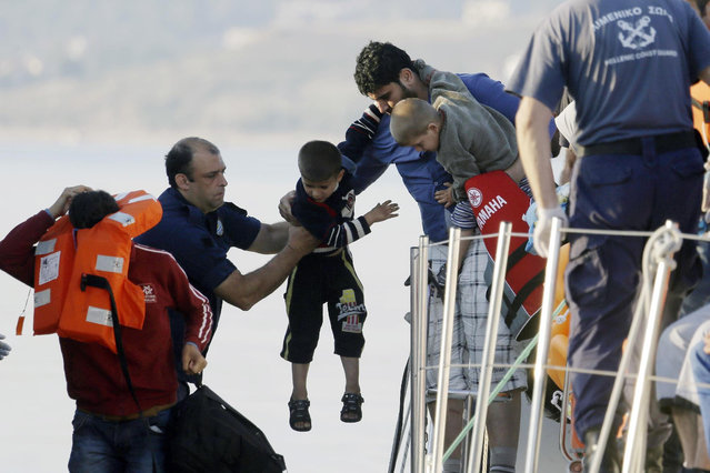 A father gives his son to a coast guard officer, second left, as he disembarks from a vessel at the port of Mitylene after being picked up by the Greek coast guard near the northeast Greek island of Lesvos on Wednesday, June 17, 2015. Around 100,000 migrants have entered Europe so far this year as Italy and Greece have borne the brunt of the surge with many more migrants expected to arrive from June through to September. (AP Photo/Thanassis Stavrakis)