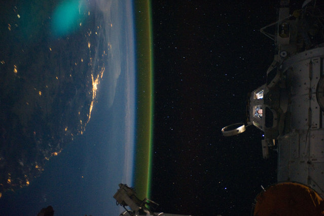 This unique photographic angle, featuring the International Space Station's Cupola and crew activity inside it, other hardware belonging to the station, city lights on Earth and airglow was captured by one of the Expedition 28 crew members. The major urban area on the coast is Brisbane, Australia. The station was passing over an area southwest of Canberra, September 15, 2011. (Photo by NASA)