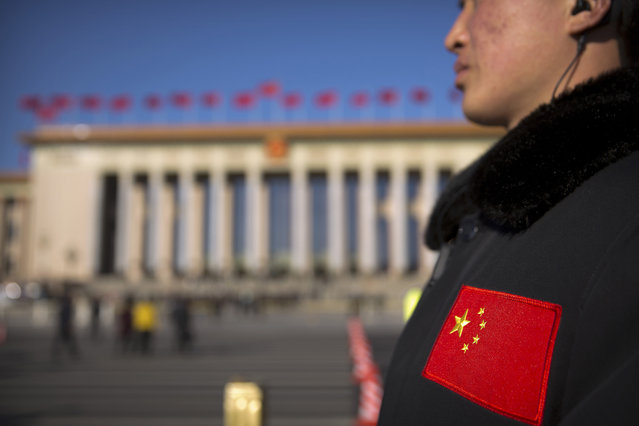In this Sunday, March 12, 2017 photo, a security official with a Chinese flag patch on his jacket stands guard outside of the Great Hall of the People before a plenary session of the National People's Congress (NPC) in Beijing. (Photo by Mark Schiefelbein/AP Photo)
