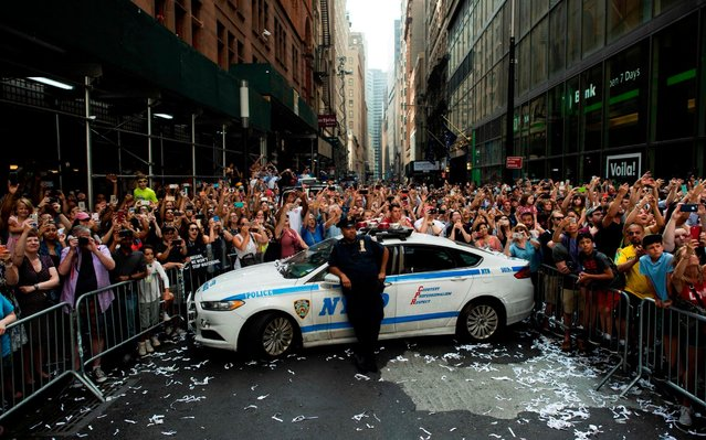 """Fans cheer on members of the World Cup-winning US women's team as they take part in a ticker tape parade for the women's World Cup champions on July 10, 2019 in New York. Tens of thousands of fans are poised to pack the streets of New York on Wednesday to salute the World Cup-winning US women's team in a ticker-tape parade. Four years after roaring fans lined the route of Lower Manhattan's fabled """"Canyon of Heroes"""" to cheer the US women winning the 2015 World Cup, the Big Apple is poised for another raucous celebration. (Photo by Johannes Eisele/AFP Photo)"""