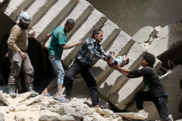 Syrian civil defence volunteers and rescuers remove a baby from under the rubble of a destroyed building following a reported air strike on the rebel-held neighbourhood of al-Kalasa in the northern Syrian city of Aleppo, on April 28, 2016. (Photo by Ameer Alhalbi/AFP Photo)
