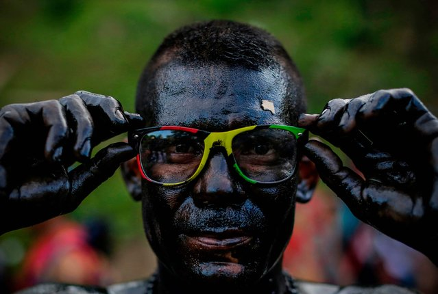 A catholic faithful smeared in burnt oil, takes part in the opening of the ten-day celebration of the Santo Domingo de Guzman festival in Managua, on August 1, 2019. (Photo by Inti Ocon/AFP Photo)